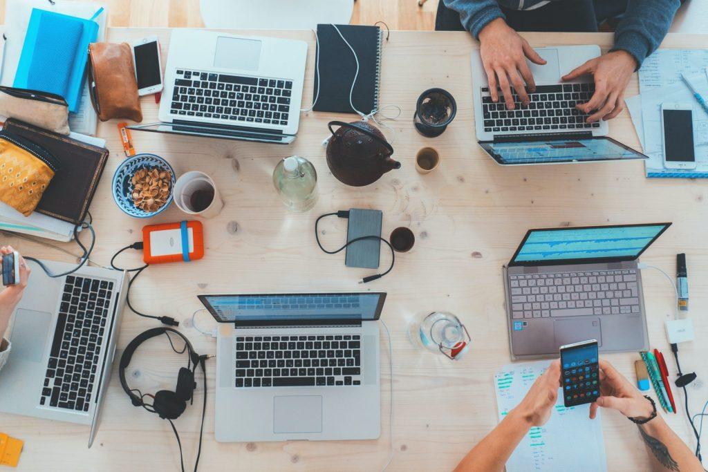 mesa com notebooks, smartphones e pessoas trabalhando