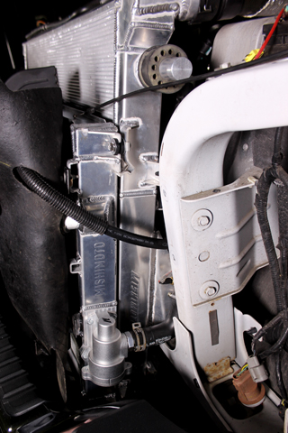 Driver's side view of our 6.7 Super Duty with Mishimoto's primary and secondary system radiators installed. The thermostat housing is pictured near the bottom.