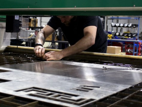 Our engineer, Mike, loads up a sheet of aluminum into our WARDJet water jet cutter