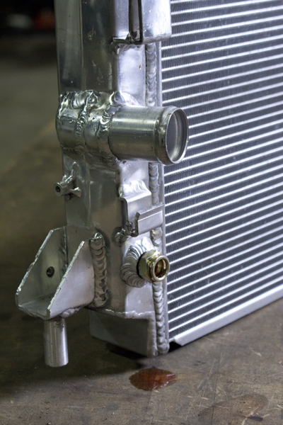 The posts on the bottom left and right (not pictured) corners align the radiator within the stock mounting brackets.