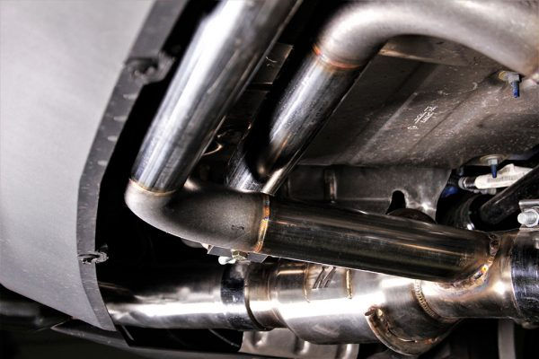 The pipes routed off of the exhaust and wrapped in the bumper act as Helmholtz resonators