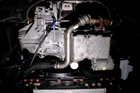 Underbody shot of the stock intercooler piping on a 2013 Ford Focus ST