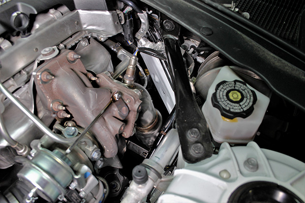 An engine bay view of the downpipe on our 2.0T