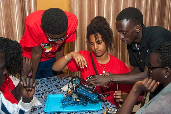 Sidy Ndao (right), assistant professor of mechanical and materials engineering, gives advice to a student team as it finishes assembling its robot at the SenEcole robotics camp in Dakar, Senegal this past March.