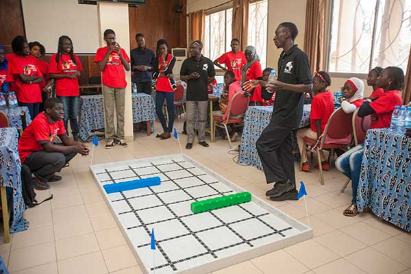 Sidy Ndao (right), assistant professor of mechanical and materials engineering, presents the competition field to the students on the third day of the SenEcole robotics camp in Dakar, Senegal this past March.