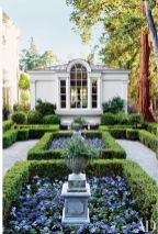 A boxwood parterre is planted with violas and petunias on the grounds of a California residence land.