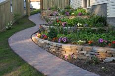 A stone garden bed looks great when paired with a stone walkway. Stones are a great way to make a multiple leveled garden bed_ as stone stacks well even on uneven ground.