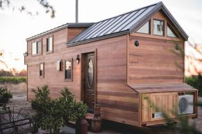 A stunning 28_ luxury tiny home from California Tiny House. Its interior features two fireplaces_ a full kitchen_ bathroom_ and a cozy loft bedroom.