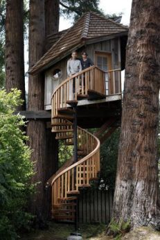 Artist Jay Nelson stands with ceramist Daria Joseph in front of the tree house with a spiral stairca...