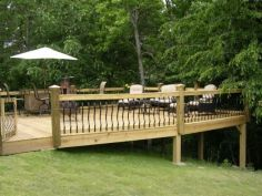 Deck built onto sloped yard_ railings