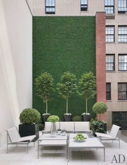 On a New York townhouse_s terrace_ a wall blanketed in faux boxwood offsets outdoor furniture by Ri.