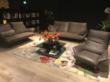 Leather-living-room-furniture-with-floral-pattern-carpet-under-glass-coffee-table