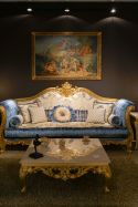rococo-blue-sofa-with-gold-frame-and-coffee-table-with-a-baroque-design-framed-wall-art-above-sofa