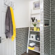 a-bathroom-clad-with-grey-tiles-with-white-furniture-and-grey-and-yellow-accessories-and-accents-looks-very-bold