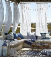a-beach-patio-with-printed-curtains-a-bench-with-bright-blue-pillows-a-wicker-table-and-a-candle-lantern-is-very-welcoming
