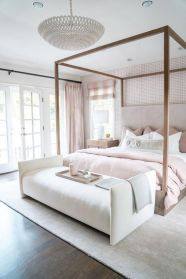 a-beautiful-feminine-bedroom-with-a-wallpaper-accent-wall-a-canopy-bed-blush-bedding-and-curtains-and-a-chic-chandelier