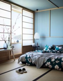 a-beautiful-zen-like-bedroom-with-traditional-Japanese-sliding-doors-a-low-bed-and-wooden-furniture-blue-walls-and-a-ceiling-floral-bedding