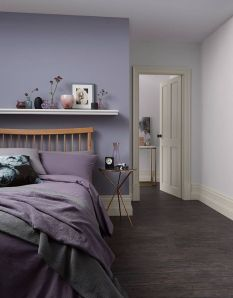 a-bedroom-with-a-purple-wall-a-wooden-bed-with-purple-and-grey-bedding-lavender-and-white-walls