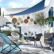 a-blue-seaside-patio-with-rugs-bold-woven-chairs-and-stools-decorative-plates-lamps-and-potted-plants