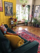 a-boho-living-room-with-a-mustard-wall-a-dark-green-sofa-bright-and-printed-pillows-potted-greenery-statement-artworks
