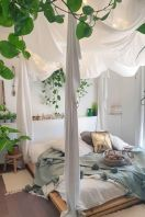 a-boho-spring-bedroom-in-neutrals-with-a-bed-on-the-floor-pastel-bedding-potted-greenery