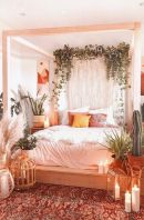 a-boho-spring-bedroom-in-neutrals-with-a-wooden-canopy-bed-potted-plants-macrame-candles-and-a-boho-rug