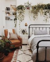 a-boho-spring-bedroom-with-a-metal-bed-a-leather-chair-neutral-and-printed-bedding-potted-greenery-and-brass-touches