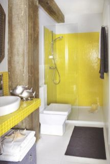 a-bold-bathroom-with-white-walls-lemon-yellow-tiles-rough-wooden-beams-grey-upholstery-and-textiles