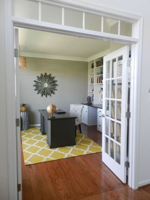 a-bold-home-office-with-a-grey-accent-wall-a-white-storage-unit-that-takes-a-whole-wall-a-black-desk-a-bright-printed-rug-and-a-sunburst-mirror
