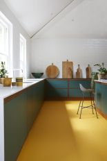 a-bold-kitchen-with-a-yellow-floor-green-cabinets-and-white-countertops-is-a-very-chic-and-cool-space-with-a-modern-feel