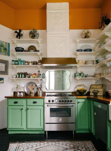 a-bold-kitchen-with-color-block-white-and-rust-wall-green-cabinets-stainless-steel-appliances-and-a-patterned-hood