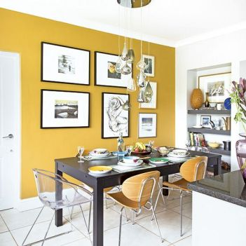 a-bold-modern-dining-room-with-a-mustard-accent-wall-a-black-table-some-pretty-chairs-niche-shelves-and-a-chic-gallery-wall