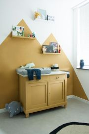 a-bold-nursery-with-mustard-color-blocking-on-the-wall-a-mustard-cabinet-shelves-toys-and-artworks-and-grey-touches