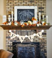a-bold-vintage-Thanksgiving-mantel-with-berries-pumpkins-and-blooms-all-faux-ones-candles-and-a-chalkboard-sign