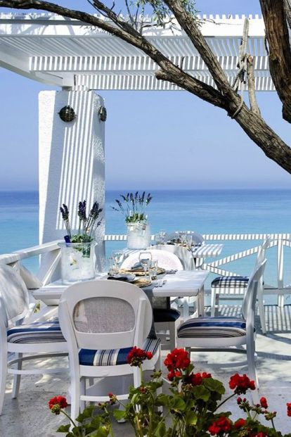 a-bright-blue-and-white-beach-patio-with-a-dining-set-bright-chairs-some-blooms-and-a-tree-and-a-fantastic-view