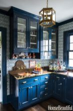 a-bright-blue-kitchen-with-blue-printed-wallpaper-bold-stained-countertops-and-a-backsplash-plus-gold-touches-here-and-there