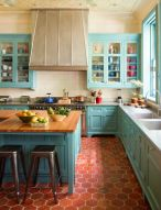 a-bright-blue-kitchen-with-terracotta-tile-on-the-floor-a-large-vintage-hood-butcher-block-countertops-and-a-patterned-ceiling