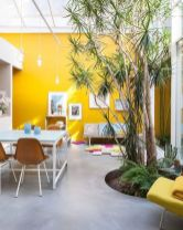 a-bright-contemporary-living-room-and-dining-room-with-a-yellow-accent-wall-catchy-furniture-living-trees-and-touches-of-blue
