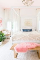 a-bright-feminine-bedroom-with-a-cnaopy-bed-a-wooden-bench-and-a-woven-chair-a-statement-plant-and-a-floral-chandelier