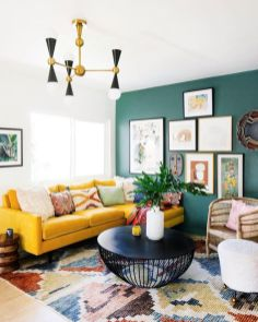 a-bright-living-room-with-a-green-wall-a-bright-yellow-sofa-a-colorful-printed-rug-a-bright-gallery-wall-and-a-mid-century-modern-chandelier