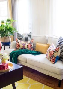 a-bright-living-room-with-a-white-sofa-accented-with-bright-pillows-a-bold-rug-and-a-dark-coffee-table-plus-greenery