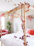 a-bright-spring-bedroom-with-a-wooden-bed-a-coral-chair-faux-cherry-blossom-covering-the-bed-and-coral-pillows