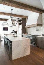 a-catchy-kitchen-with-dark-cabinetry-a-white-stone-kitchen-island-rough-wooden-beams-and-a-refined-chandelier