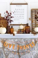 a-chic-and-bold-Thanksgiving-mantel-with-white-pumpkins-dark-leaves-apothecary-bottles-a-quote-and-some-wooden-decor
