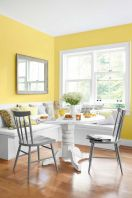 a-colorful-dining-nook-with-yellow-walls-a-white-corner-seat-a-white-table-grey-chairs-and-grey-and-yellow-pillows