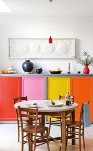 a-colorful-kitchen-with-bold-doors-and-a-round-table-wooden-chairs-and-a-pretty-textural-artwork-and-red-touches