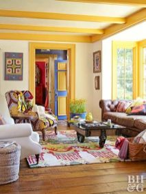 a-colorful-living-room-with-yellow-beams-and-frames-a-brown-leather-sofa-colorful-chairs-and-a-rug-a-coffee-table-on-casters