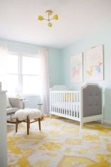 a-colorful-nursery-with-light-blue-walls-neutral-furniture-a-colorful-gallery-wall-a-printed-rug-and-curtains-plus-a-yellow-chandelier