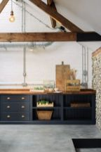a-contemporary-kitchen-with-navy-cabinets-a-white-brick-wall-wooden-beams-and-exposed-pipes-for-an-eye-catchy-touch