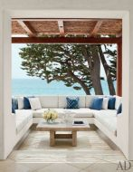 a-contemporary-seaside-terrace-with-a-U-shaped-bench-and-blue-and-white-pillows-plus-a-gorgeous-sea-view